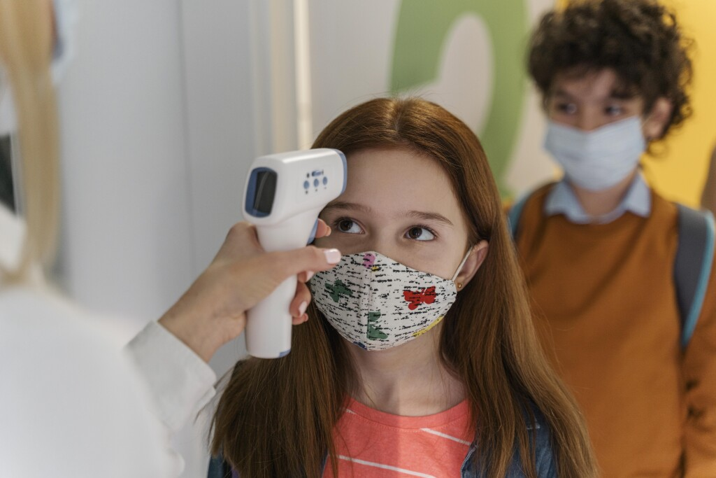 teacher-with-medical-mask-checking-children-s-temperature-in-school